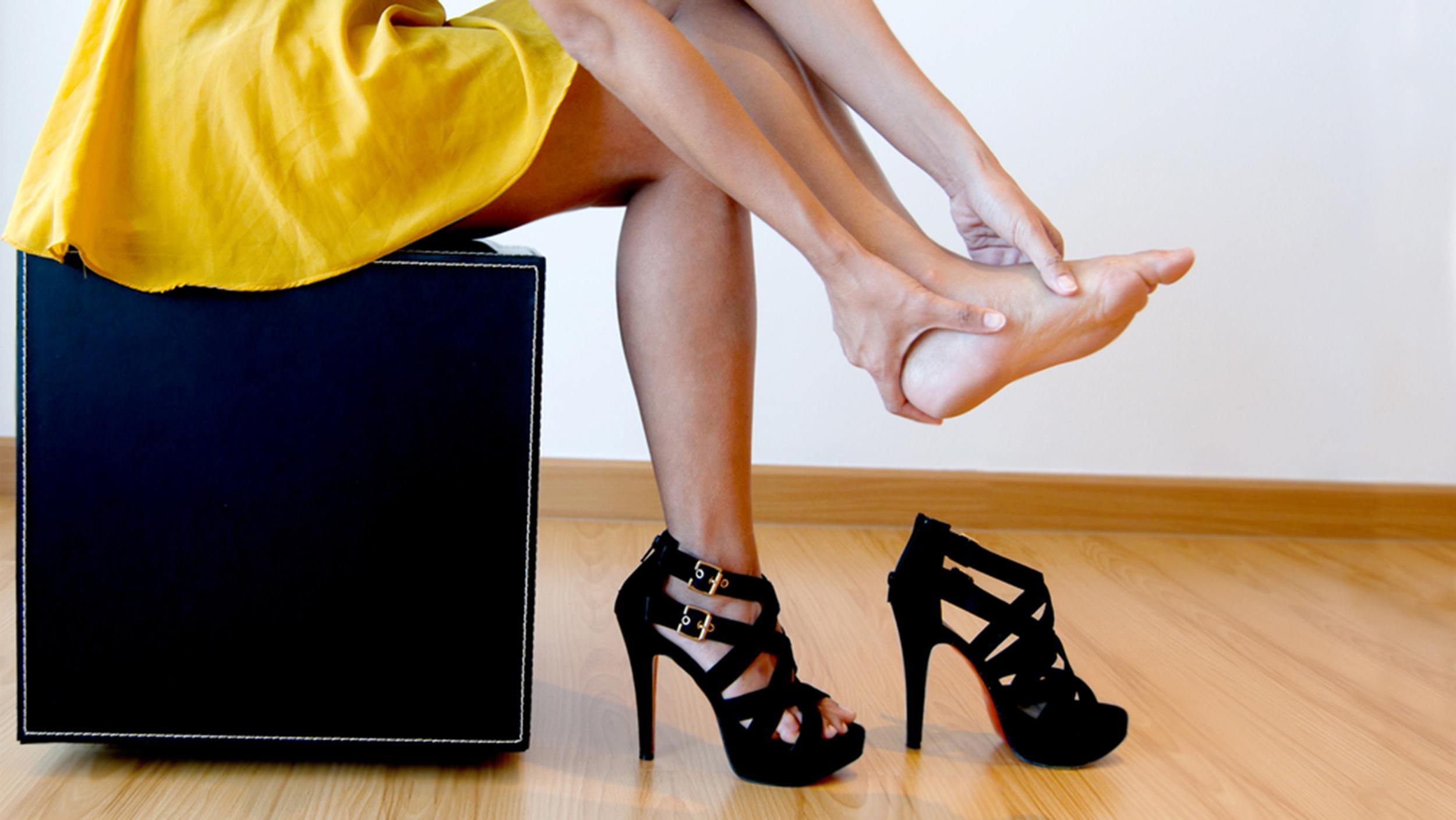 женщина сняла обувь и массирует ногу