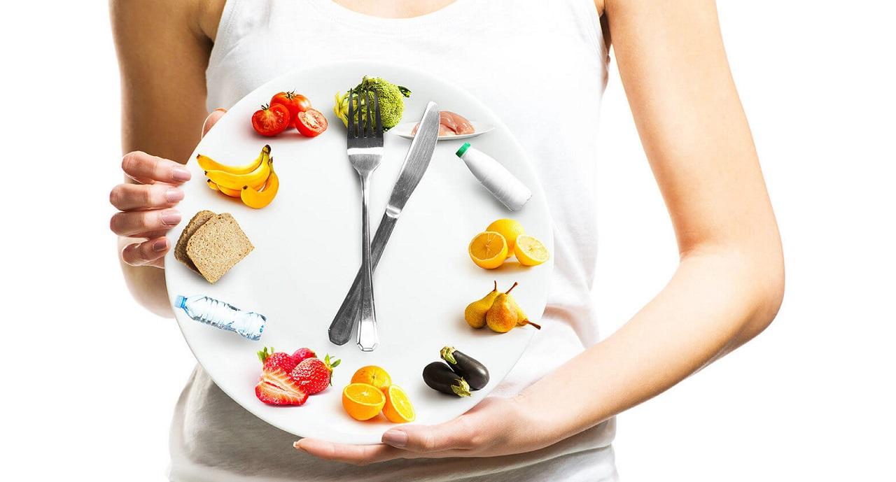 девушка держит тарелку с овощами и фруктами вилкой и ножом